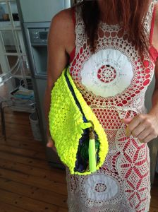 Lulu holds one of her newest designs not yet in stores, an oversized crochet woven clutch available in neon yellow, pink and orange lined in African fabrics.